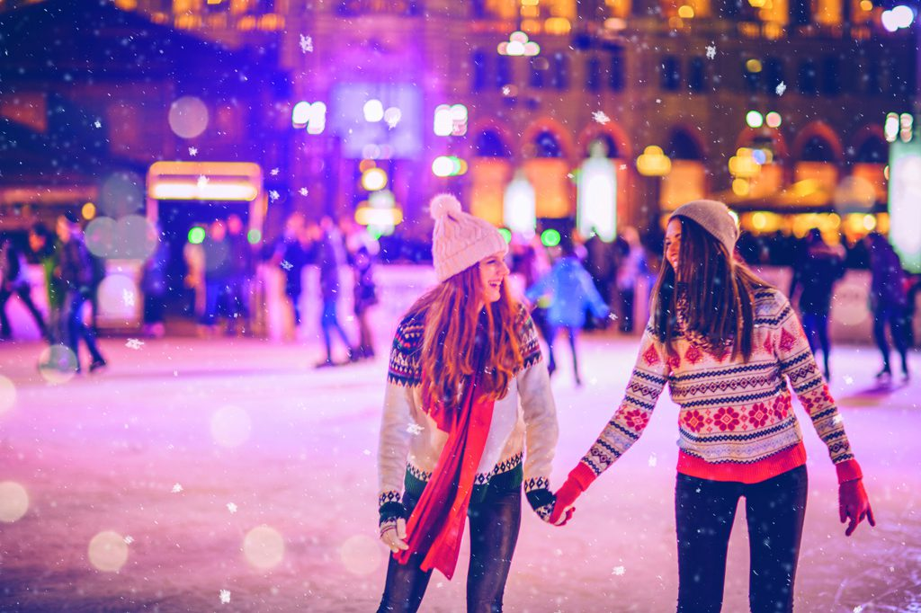 Friends having so much fun while ice skating at night. Wearing warm clothing. City is decorated with christmas lights.